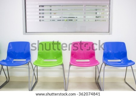 Brightly colored chairs arranged neatly in a small conference room. - stock photo