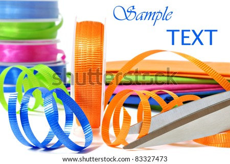 Brightly colored curling ribbon with scissors and wrapping paper on white background with copy space.  Macro with shallow dof. - stock photo