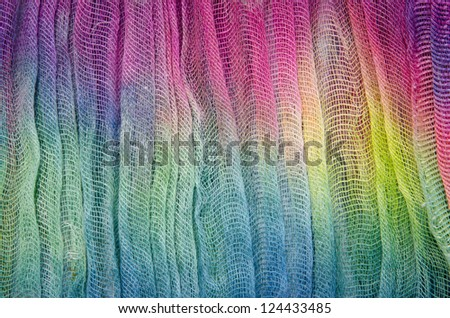 Brightly colored dyed fabric with a loose weave. - stock photo