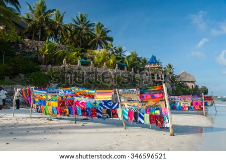 brightly colored fabric for sale on a white sand beach against a beautiful blue sky