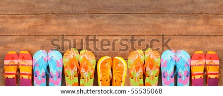 Brightly colored flip-flops on wood deck - stock photo