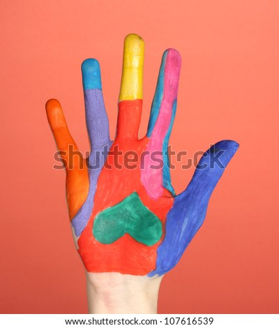Brightly colored hand on red background close-up