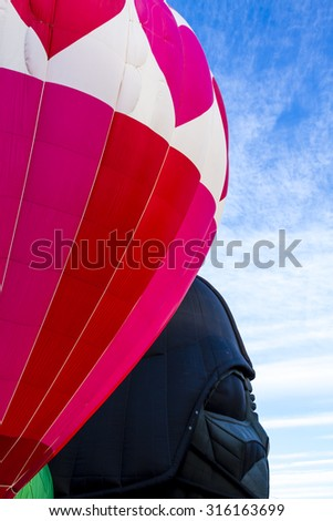 Brightly colored hot air balloon against blue morning sky getting inflated before take off - stock photo