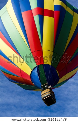 Brightly colored hot air balloon against blue morning sky just after take off