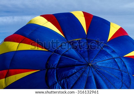 Brightly colored hot air balloon against blue morning sky on the ground before take off - stock photo
