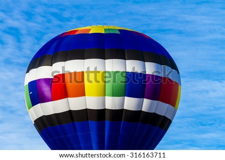 Brightly colored hot air balloon against blue morning sky on the ground before take off and balloon in the air - stock photo