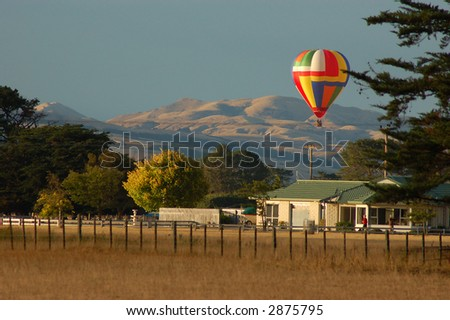 Brightly colored Hot air balloon over farmland - stock photo