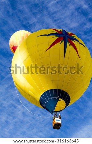Brightly colored hot air balloons against blue morning sky just after take off - stock photo