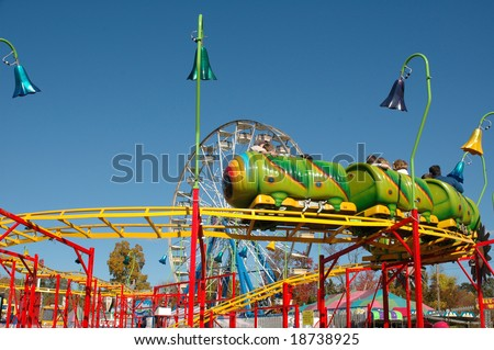 Brightly colored kiddie rides at a county fair - stock photo