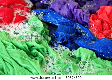 Brightly colored laundry with sudsy water in washing machine.  Close-up with shallow dof. - stock photo