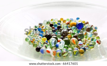 Brightly colored marbles in different shades in a bright glass bowl - stock photo