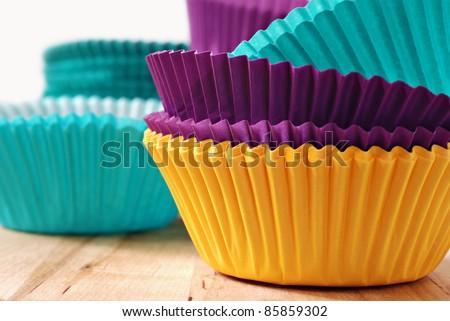 Brightly colored paper baking cups for cupcakes or muffins.  Macro with shallow dof. - stock photo