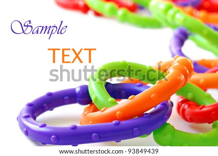 Brightly colored plastic chain links - a classic baby toy and teething ring also used to attach toys to stroller - on white background with copy space.  Macro with shallow dof. - stock photo