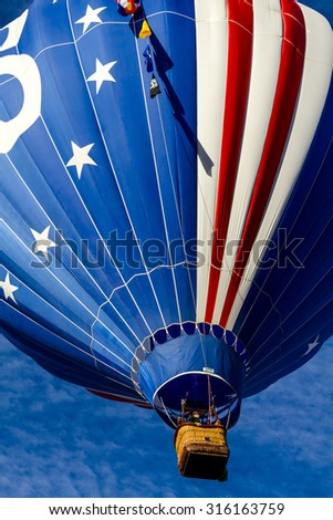 Brightly colored red, white and blue hot air balloon against blue morning sky just after take off - stock photo