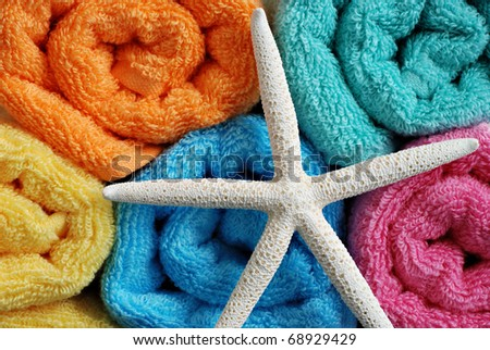 Brightly colored rolled towels with white finger starfish. - stock photo