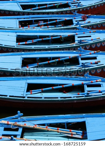 Brightly colored row boats lined up on the Ganges river in Varanasi, Uttar Pradesh, India.  - stock photo