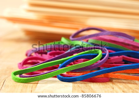Brightly colored rubber bands with stack of manilla folders in soft focus in background.  Macro with extremely shallow dof. - stock photo