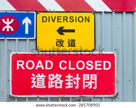 Brightly colored traffic signs announce a detour due to construction and development along a central street in downtown Hong Kong, China. - stock photo
