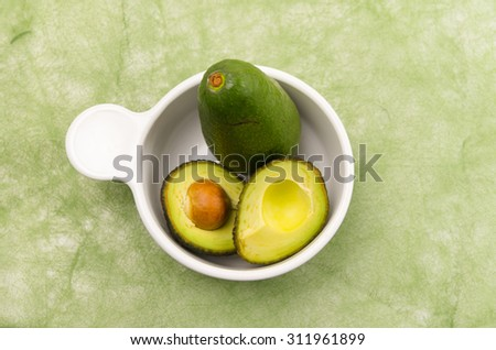 brightly colored two avocados in a white bowl with one cut into halfs and blurry green background - stock photo