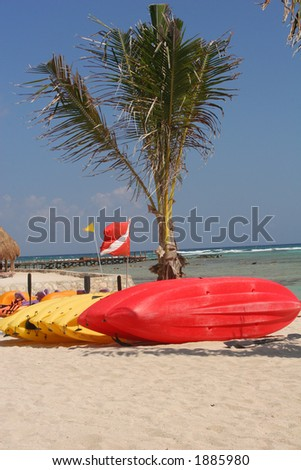 Brightly colored water sports equipment on the beach with diver flag. - stock photo
