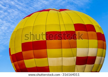 Brightly colored yellow and red hot air balloon against blue morning sky tethered to the ground before take off - stock photo