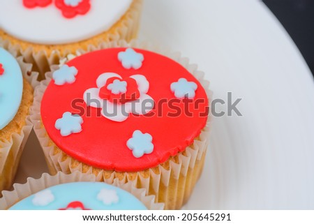 Brightly coloured cupcakes with flower design on a white plate - stock photo