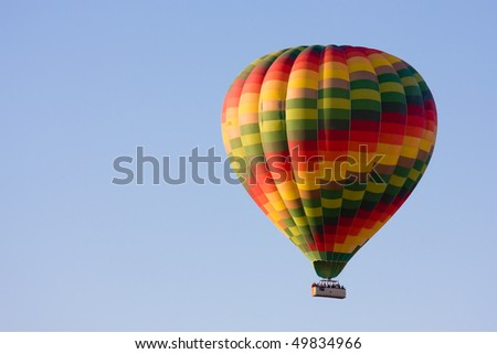 Brightly coloured hot air balloon against a clear blue sky