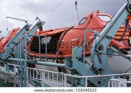 Brightly coloured Lifeboats secured on a ferry - stock photo