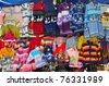 Brightly coloured woollen jumpers hanging on market stall - stock photo