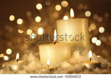 Brightly lit candles in wet snow against sparkly background - stock photo