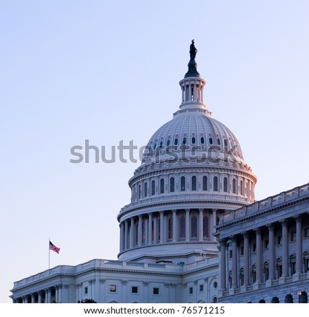 Brightly lit dawn sky behind the illuminated dome of the Capitol in Washington DC with the Statue of Freedom in the sunlight - stock photo