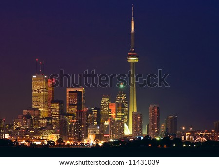 Brightly lit skyscrapers of Toronto's financial district with the CN Tower and a silhouette of the waterfront - stock photo