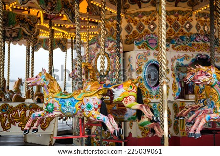 Brightly painted horses on a vintage carousel or merry-go-round at a fairground for children to ride as they go round and up and down imitating galloping - stock photo