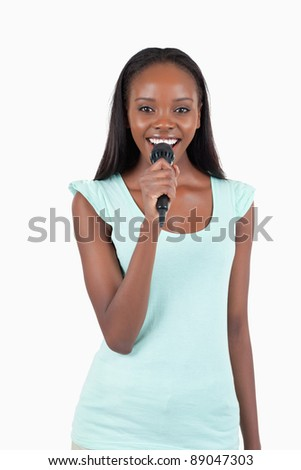 Brightly smiling young female singer against a white background