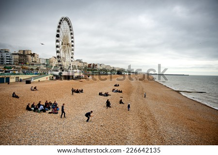 BRIGHTON - APRIL 06 - View down the golden sand of Brighton beachfront to the ferris wheel and amusement park with groups of people on the beach on April 06, 2014 - stock photo