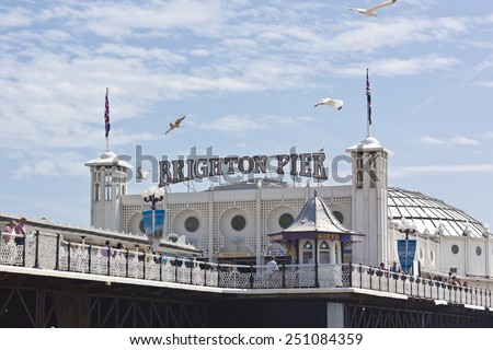 BRIGHTON BEACH, GREAT BRITAIN - JUNE 13: People enjoy a sunny day at the historic Brighton Pier on June 13, 2009. The beach between the West and Palace Piers has bars, restaurants, sports facilities. - stock photo