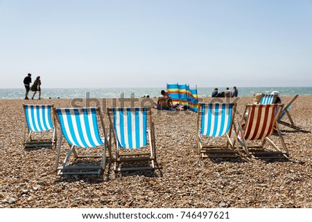 BRIGHTON, GREAT BRITAIN   JUN 17, 2017: Classic Deckchairs And People  Sunbathing And