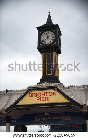 Brighton Pier Clock Tower Under Cloudy Skies in Brighton, England - stock photo