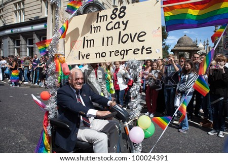 BRIGHTON, UK - AUG 13. An 88 years old gay man join the pride parade with his scooter and 'life with no regret' sign at Brighton Pride Festival on August 13, 2011. - stock photo