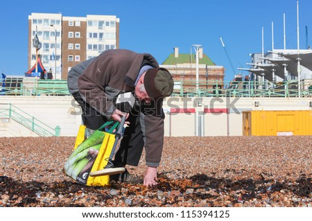 BRIGHTON, UK - FEBRUARY 8, 2011: Pensioner looking for metal objects on beach with metal detector on February 8, 2011 in Brighton, UK. An estimated 2 million pensioners living below the breadline. - stock photo