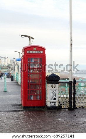 A Traditional Red Telephone Box With Picture Of