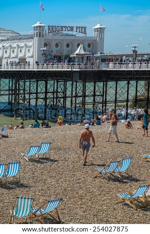 BRIGHTON, UK- JULY 28, 2013: People enjoying a rare sunny day on Brighton Beach in front of the famous Pier on July 28th, 2013. - stock photo