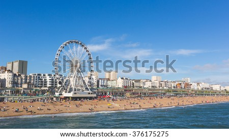 Brighton view of seaside from the pier. Panoramic shot with the famous ferris wheel, the stones beach with unrecognizable persons on a sunny summer day. - stock photo