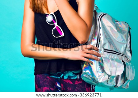 Brigit fashion details, stylish sportive woman wearing crazy mirrored silver backpack, printed pants and clear vintage sunglasses, mint background. - stock photo