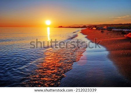 Brilliant and colorful sandy beach sunrise with breaking wave and sea foam - stock photo