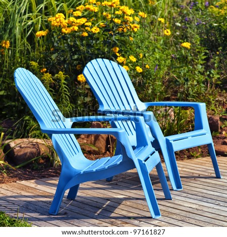 brilliant blue plastic outdoor adirondack chairs on the deck in a summer garden