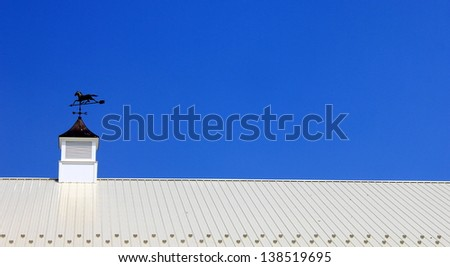 Brilliant blue summer sky and the vivid color of white metal roofing with weathervane cupola on top - stock photo