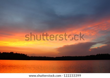 Brilliant colors of sunset over a northwoods Wisconsin Lake - stock photo