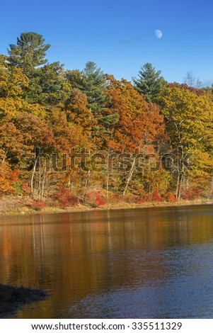 Brilliant fall foliage on the shoreline of Mansfield Lake in Connecticut, with reflections on the calm water, and the moon rising above in a blue sky. - stock photo