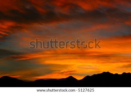 Brilliant, luminous shades of yellow, and orange streak the skies over the Rocky Mountains during an autumn sunrise. - stock photo